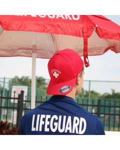Front of the Lifeguard Flexfit® Cap in Lifeguard Red with White Lifeguard Logo Worn